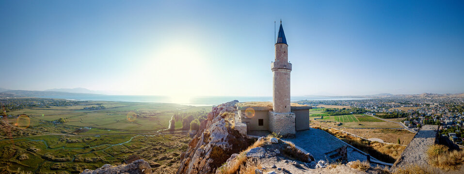 Sunset over castle of Van and Van lake with a minaret. Van castle on sunset. Fortress built during the 9th to 7th centuries BC. Turkey. Van Lake in the background
