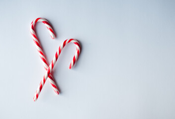 Close up of two candy canes arranged on a plain white background.