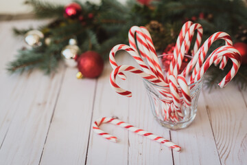 Glass full of candy canes against a Christmas backdrop.