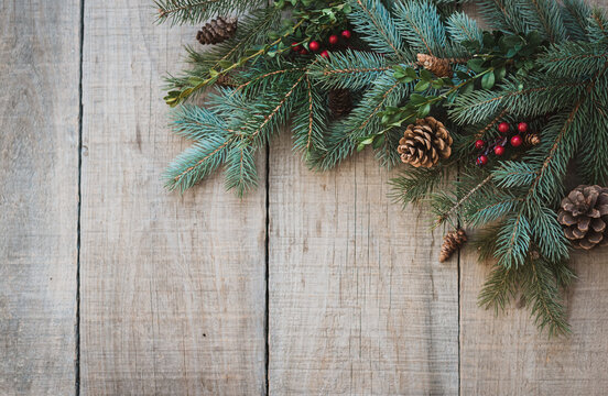 Winter greenery, pinecones and berries against rustic wood backdrop.