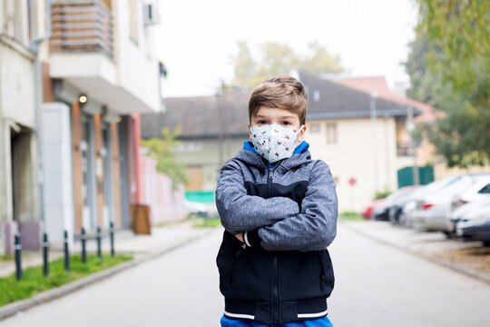 Little boy with arms crossed wearing kn95 face mask outdoors.