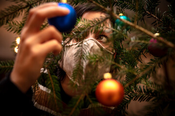 Woman is decoration a christmas tree with baubles while she wearing a face mask, corona