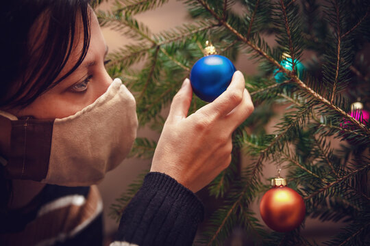 Woman wearing a face mask and is decoration a christmas tree with baubles or balls