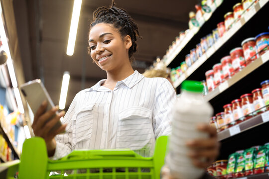 Lady Using Cellphone With Grocery Shopping Application In Supermarket