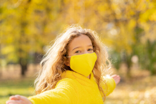 Happy child wearing protective mask in autumn park