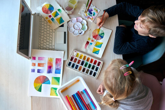 Children painting pictures with watercolor paints during art lesson. Pupils are concentrating on drawing with brush. Watercolor color wheel and palette. Color theory beginner hobby lessons