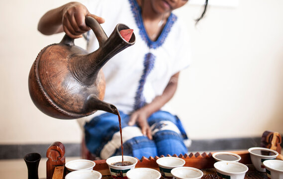 Closeup of womans hand as she serves coffee from a traditional pot in Ethiopia