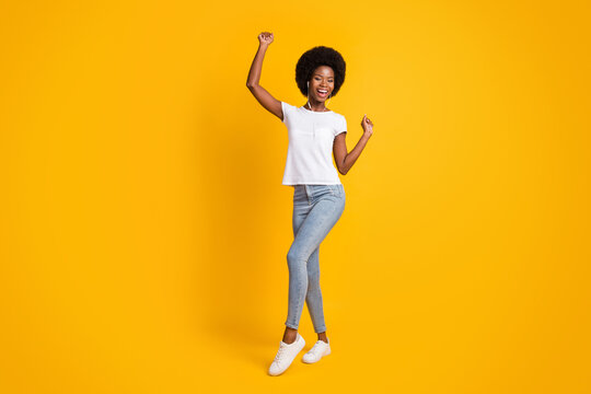 Full length body size photo of young girl with black skin listening music with headphones wearing casual outfit smiling isolated on bright yellow color background