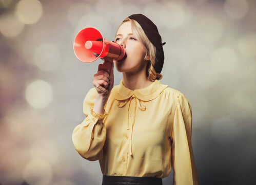 Beautiful girl in vintage clothes with megaphone on gray background