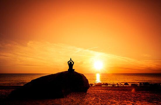Frau bei sonnenuntergang am Strand in Yoga Pose