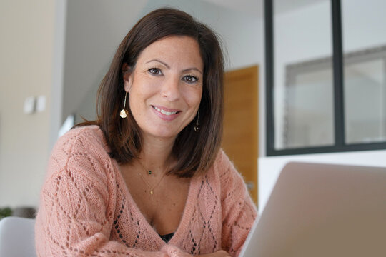 young brunette latin woman working on laptop at home