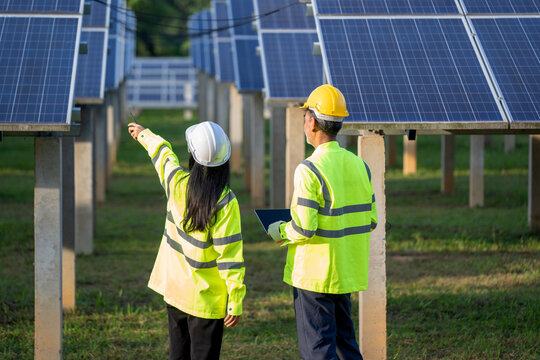 Technicians and engineer in long sleeve shirts reflective vests and hard hats discussing something about solar panel power,Solar power plant to innovation of green energy for life.