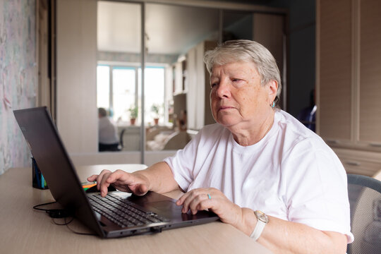 senior woman learning to work on a computer while sitting at a laptop at home