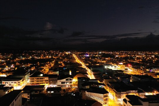 Aerial view of a city at night showing the many buildings being lit and a the bright mainstreet