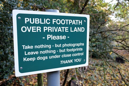 Sign saying public footpath over private land, please take nothing but photographs, leave nothing but footprints, keep dogs under close control, thank you