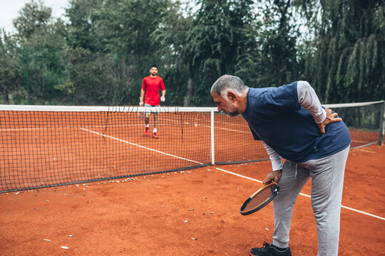middle aged man having backache injury on tennis court