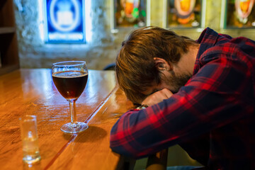 Alcoholism concept. A young man sits alone at the bar in a pub. Social problem. Fight against alcohol addiction, crisis, depression.