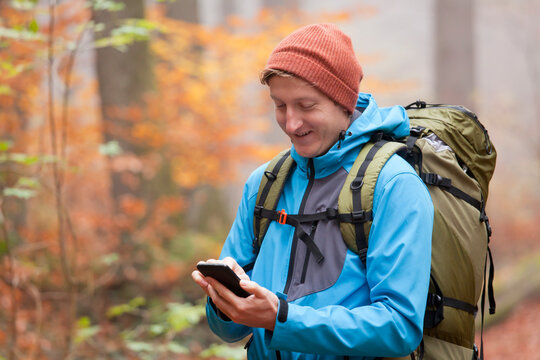 Young backpacker looking at smartpone in a colorful forest in autumn
