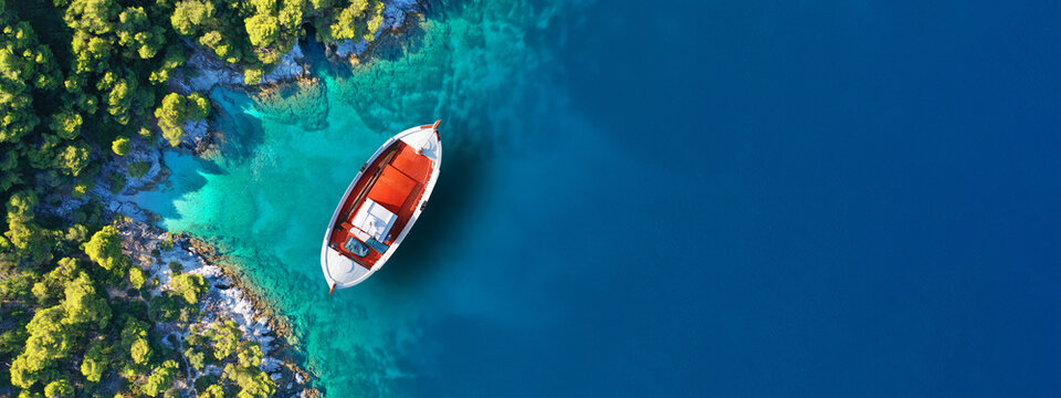 Aerial drone ultra wide panoramic photo of traditional wooden fishing boat anchored in Ionian island turquoise sea, Greece
