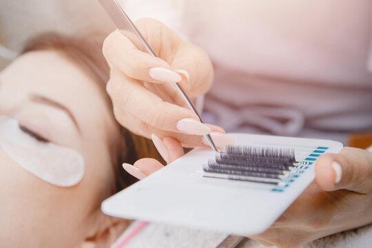 Eyelash extension procedure. Woman master making fake long lash