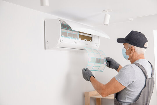 Brush cleaning Air conditioner from dust. Worker in gloves and medical mask checks filter