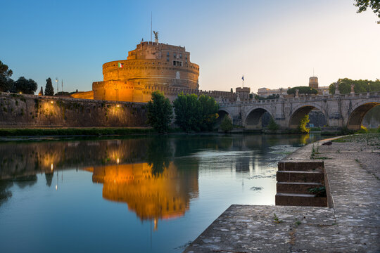 Night to sunrise long exposure of Castel Sant'Angelo (Castle of the Holy Angel), an ancient tomb and fortress, illuminated at night and reflecting on the Tiber river, with the Bridge of the Holy Angel