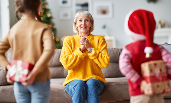 happy family grandchildren gives a cheerful smiling grandmother a Christmas gift.