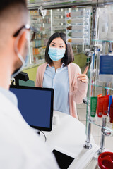 asian woman in medical mask pointing with finger while showing one to pharmacist on blurred...