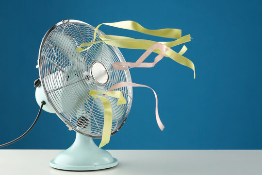 Electric fan on white table against blue background. Summer heat