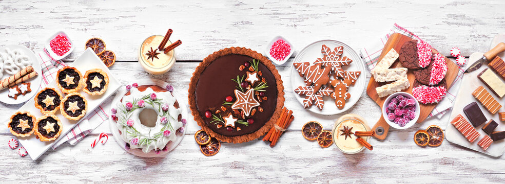 Various Christmas holiday desserts and sweets. Overhead view table scene on a white wood banner background. Bundt cake, chocolate pie, mincemeat tarts, cookies, fudge and eggnog.