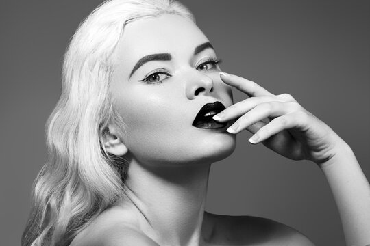 Beautiful young sexy woman with vintage make-up, hairstyle. Pin-up with red lips. American diva style. Black and white