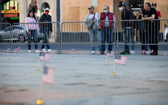 People wearing face protective masks look at U.S. Flags on the forecourt of the TCL Chinese theatre to salute celebrities who have served in the U.S. Military ahead of Veterans Day during the outbreak of the coronavirus disease (COVID-19), in Los Angeles
