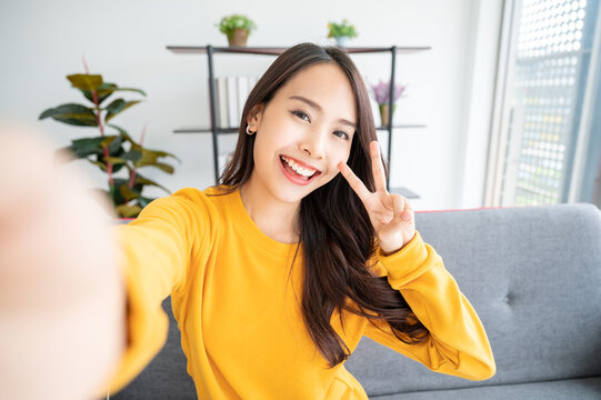 Pretty young asian female with big smile sitting at living room. She having fun taking light cheerful selfie on blurred background