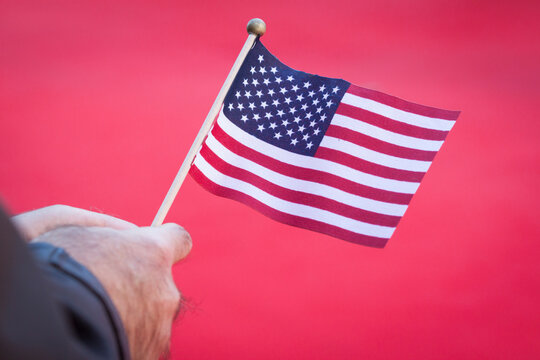 Hand holding a small American Flag on a red background.