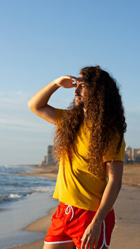 Vertical shot of a young man with long curly hair standing on the beach