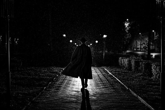 dark silhouette of a male detective in a coat and hat in the rain on a night street