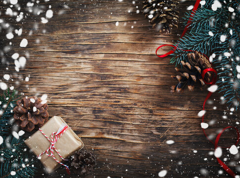 Christmas blue fir tree with pine cones and gift on wooden background for copy space