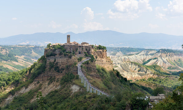 Cività di Bagnoregio sitting on a limestone cliff and slowly decaying. A medieval town center with a church and old houses holds on the plateau among a scenic eroded landscape