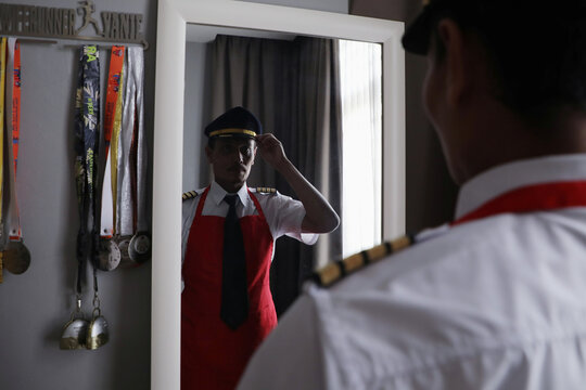 Malaysian former pilot Azrin Mohamad Zawawi puts on uniform before open his food stall, at his home in Subang Jaya