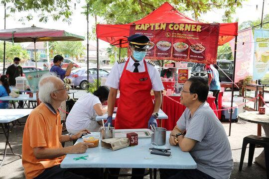 Malaysian former pilot Azrin Mohamad Zawawi talks to customers at his food stall in Subang Jaya