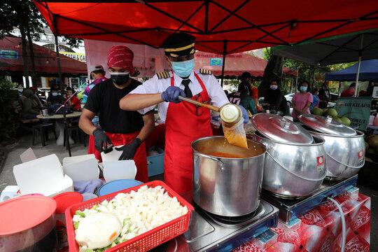 Malaysian former pilot Azrin Mohamad Zawawi prepares food at his food stall in Subang Jaya