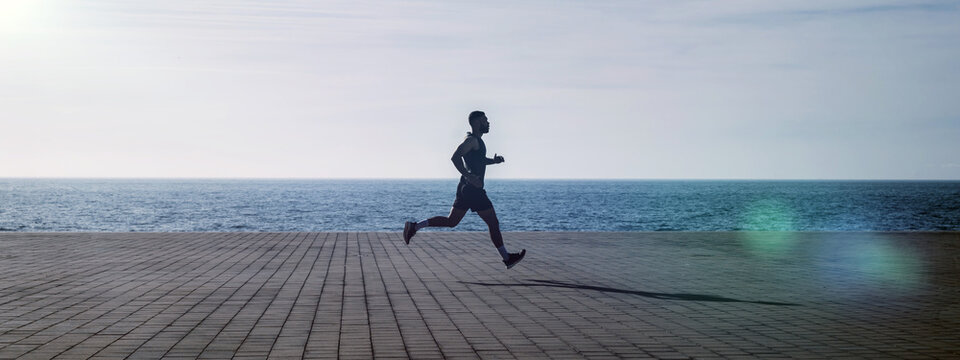 Fit young man running along seafront. Male runner jogging early in the morning. Fitness training outdoors. Workout during lockdown outside the gym.