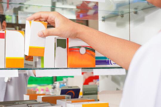 Over shoulder shot pharmacist holding medicine box on shelf drug  in pharmacy drugstore.