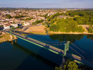 View from drone of small French town of Marmande with suspension bridge over Garonne river on...