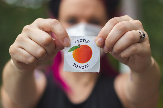 """LAWRENCEVILLE, UNITED STATES - Oct 29, 2020: A Georgia voter  displays her """"I Voted"""" sticker after voting in the 2020 Presidential Election."""
