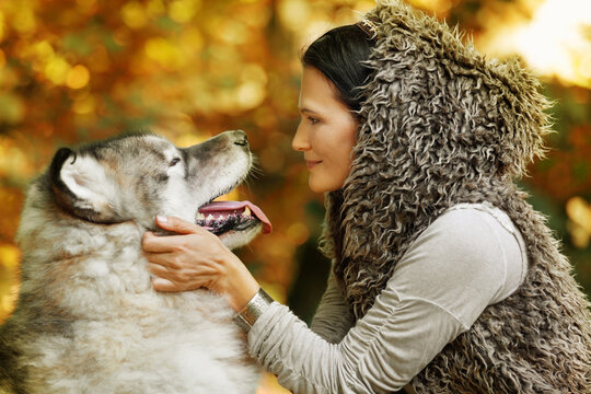 Portrait of a white woman with an Alaskan Malamute dog in the forest