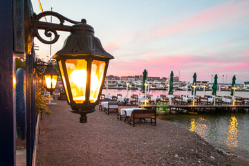 Deserted promenade with piers and cafes during beautiful fiery sunrise or sunset on the sea coast. Elegant street lamp is lit in foreground. Fotomurales