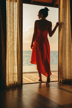 Woman enjoying the sea view standing on an overwater villa