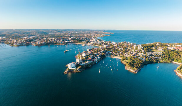 Aerial evening view of Manly, a suburb of northern Sydney in New South Wales, Australia. Little Manly & Collins Beach in the foreground, Manly Harbour, Manly Beach and Northern Beaches in background.
