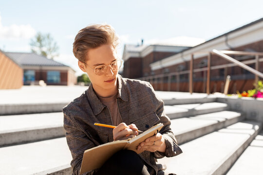 leisure, education and people concept - young man or teenage boy in glasses with notebook, diary or sketchbook writing or drawing in city
